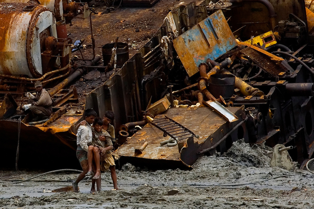 An injured labor is carried out by his colleagues  in a ship breaking yard in Chittagong, Bangladesh.