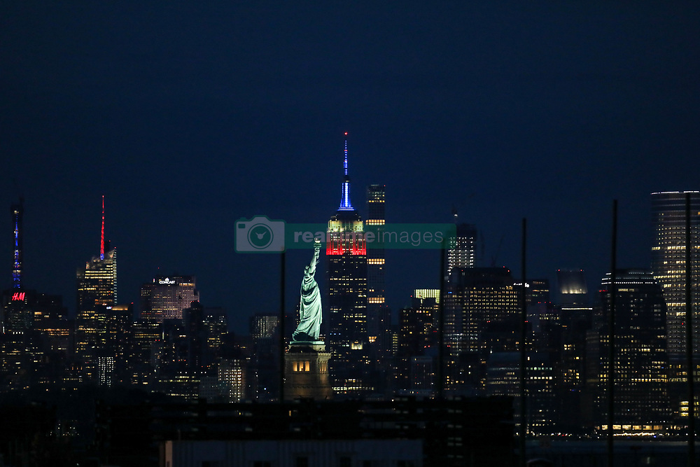 May 27, 2019 - New York, New York, United States - The Empire State Building stands next to the Statue of Liberty as it is lit in red, white and blue for Memorial Day in New York City on May 28, 2019 as seen from Bayonne, New Jersey. (Credit Image: © William Volcov/ZUMA Wire)