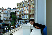 Child (9 years old) leaning over hotel balcony, overlooking street in Opatija, Croatia