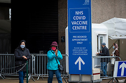 © Licensed to London News Pictures. 15/02/2021. LONDON, UK.  Women depart the mass vaccination centre at the Olympic Office Centre in Wembley, north London after being vaccinated.  Over the weekend, the UK government achieved its target of administering 15 million Covid-19 first doses by 15 February and the goal now is to vaccinate everyone over aged 50 by the end of April.  Photo credit: Stephen Chung/LNP