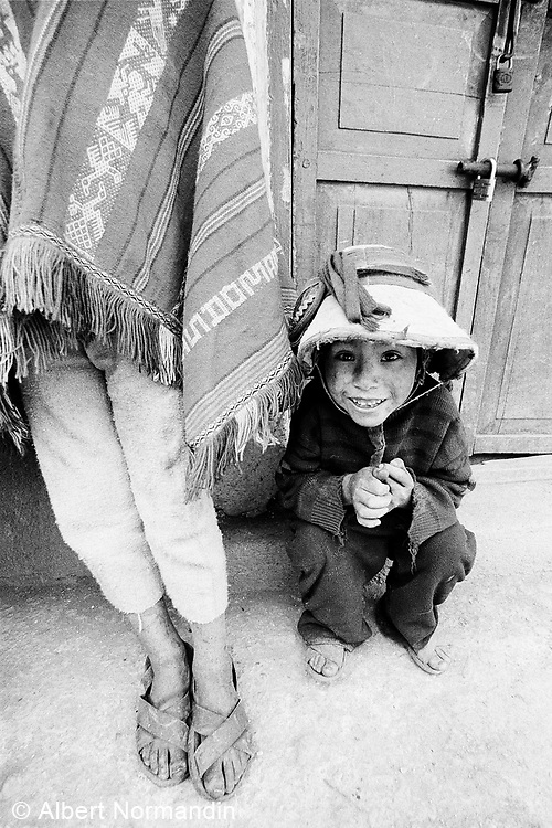 Young boy hiding behind another in traditional clothing