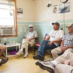 "August 4, 2017 - Tangier Island, VA - <br /> Inside the ""Situation Room,""  (named after a small briefing room in the White House) is a small room inside the former Tangier Island health clinic, where watermen gather at the end of the day to ""solve all the world's problems,"" according to Tangier Island Mayor James ""Ooker"" Eskridge (center).  From left to right, George Cannon, Richard Pruitt, Mayor Eskridge, and Danny McCready, right, discuss the day's latest.  Photo by Susana Raab/Institute"