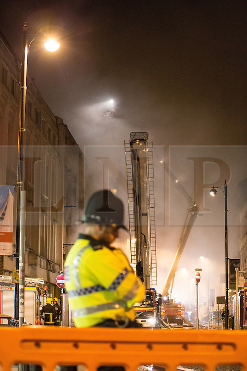 © Licensed to London News Pictures . 13/07/2013 . Manchester , UK . A policeman guards the scene and ensures people don't wonder near to the fire . A fire fighter is dead and two 15 year old girls are under arrest on suspicion of manslaughter after a blaze in Manchester yesterday (Saturday 13th July) . More than 60 fire fighters tackled a blaze at Paul's Hair World on Oldham Street in Manchester City Centre late in to the night (Saturday 13th July 2013) . Twelve crews from four stations were deployed . Several streets in a block in the city centre are sealed off . Photo credit : Joel Goodman/LNP
