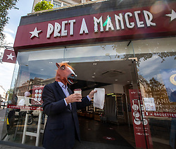 © Licensed to London News Pictures. 23/07/2020. London, UK. A man buys a takeaway from Pret A Manger in Chelsea while wearing a horses head mask. Face masks will be compulsory in shops, takeaway cafes and supermarkets from 24th July and enforced by the Police, with anyone who fails to wear one liable to a £100 fine. Photo credit: Alex Lentati/LNP