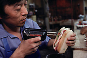 A worker uses a soldering gun to glue together plastic cheese and meat in a plastic sandwich. Iwasaki Co. Ltd, Tokyo, Japan.