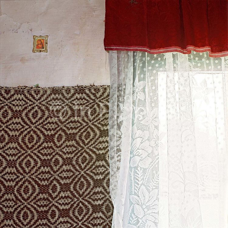 Interior of a sheepfold with religious icon and woollen weaving on the wall and net curtains at the window, Lunca Ilvei, Romania