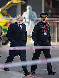 © Licensed to London News Pictures. 30/11/2019. London, UK. Prime Minister Boris Johnson visits the scene of the  London Bridge terrorist attack with Commissioner of City of London Police Ian Dyson (R) as a forensics officer gathers evidence (rear). Two people were killed and three injured after the attacker, named by police as 28-year-old Usman Khan stabbed a man and a woman to death on London Bridge. Photo credit: Peter Macdiarmid/LNP