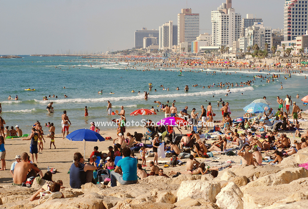 Israel, Tel Aviv, A crowd of people relaxing and cooling off on the Tel Aviv beach.