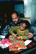 African American father age 40 helping son age 6 wrap Christmas gifts.  St Paul Minnesota USA