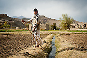 A one-legged Afghan youth watches a passing American patrol.