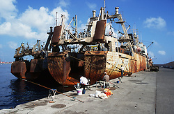 Fishing from the Dique Reina Sofia; Las Palmas harbour; Gran Canaria; Canary islands; Spain; with rusting trawler in background,