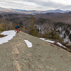 A man and woman hiking on the ledges of Huckleberry Mountain in South Johnsburg, New York. Adirondack Mountains.