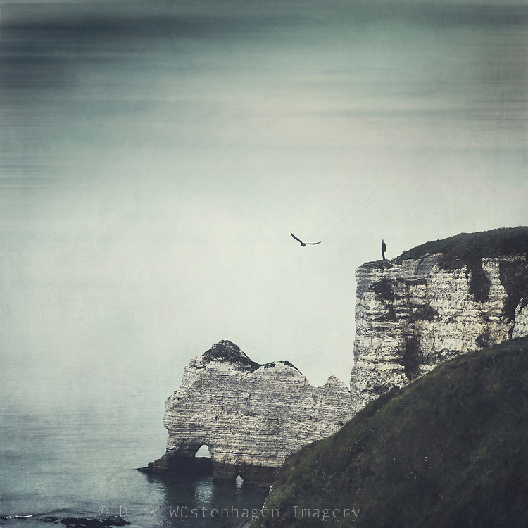 Man standing on the edge of the famous chalk cliffs near Etretat, Normandy, France