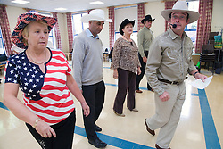 Group of older people line dancing,
