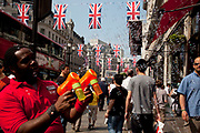A Hamley's toy shop employee blows bubbles out on the street under Royal Wedding Union flags on Regent Street, London. A display of 200 giant Union Jack Flags run all the way along from Piccadilly Circus to beyond Oxford Circus. Each flag is 4 x 2.5 metres in size and hang from 22 crossings to celebrate the Royal Wedding, recreating a majestic architectural view of one of the world's most famous historical shopping thoroughfares.