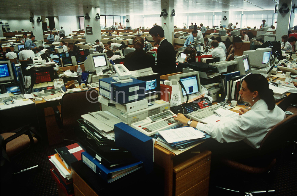 In Europes largest currency trading floor at National Westminster Bank, a 1990s female banker works at her computer at  in the City of London aka The Square Mile, the capitals financial centre, on 20th May 1993, in London, England.