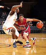 Nov 6, 2010; Charlottesville, VA, USA; Roanoke College g Melvin Felix (12) drives into Virginia Cavaliers g KT Harrell (24) Saturday afternoon in exhibition action at John Paul Jones Arena. The Virginia men's basketball team recorded an 82-50 victory over Roanoke College.