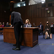 An aide withe the Senate Judiciary Committee attempts to tx the microphone of President Donald Trump's Supreme Court nominee Judge Amy Coney Barrett during the third day of her Senate Judiciary confirmation hearing on Wednesday, October 14, 2020.