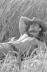 shirtless cowboy relaxing in a field