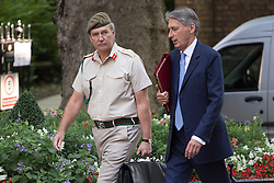 © licensed to London News Pictures. London, UK 28/08/2013. The Chief of the Defense Staff General Sir Nick Houghton (left) and Defence Secretary Philip Hammond arriving Downing Street, London on Wednesday, 28 August 2013 to attend a meeting of the National Security Council regarding the Syrian crisis. Photo credit: Tolga Akmen/LNP