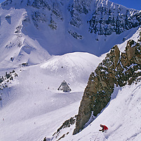 A skier descends off-piste chutes in front of Lone Mountain.