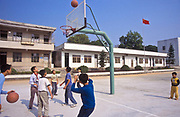 Primary school children in a mid-morning break play basket ball amongst themselves, outside Huizhou city, China