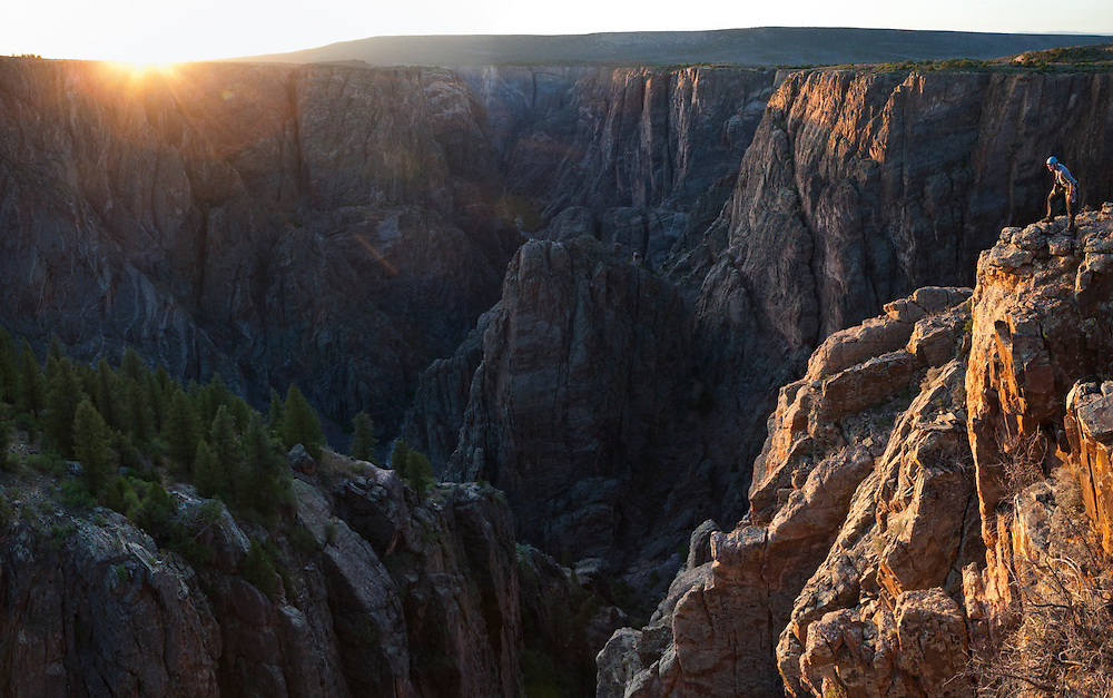 Obadiah Reid peers over the canyon rim at Island Peaks in Black Canyon of the Gunnison National Park, Colorado.
