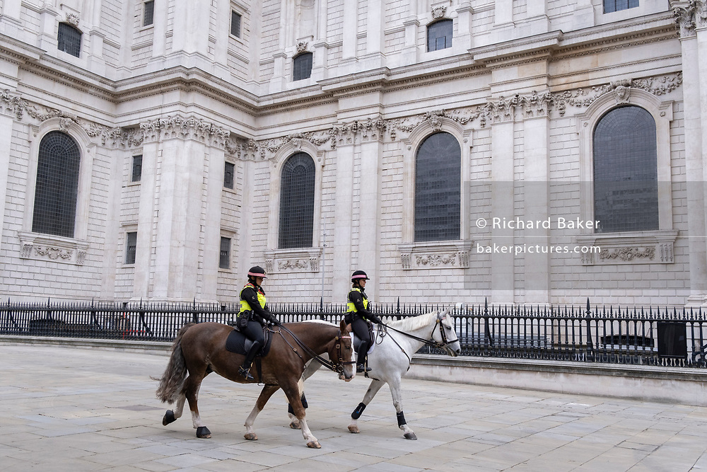 Beneath the architecture of Wren's St Paul's Cathedral, two Women Officers with the City of London Police, ride their horses on a routine daily patrol through the City of London, the capital's financial district, on 22nd June 2021, in London, England.