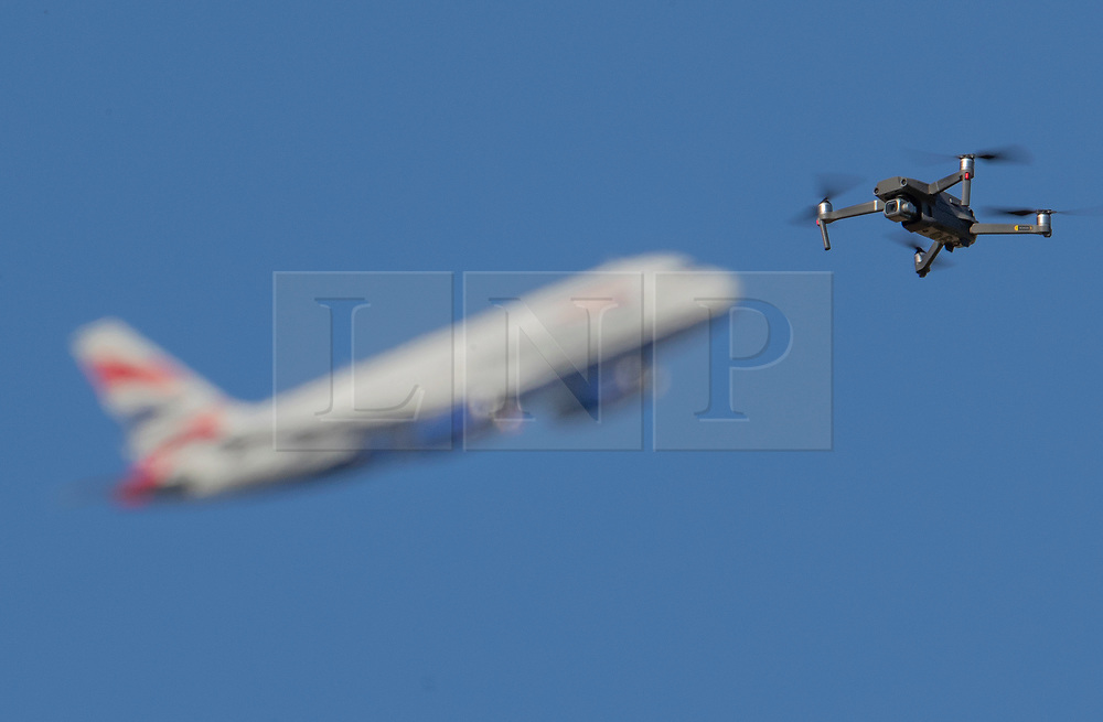 NOTE TO EDITORS Drone flown legally by a qualified drone pilot 2-3 miles from Heathrow © Licensed to London News Pictures. 18/09/2019. London, UK. Further arrests of Heathrow Pause activists have reportedly been made today during an attempt to fly toy drones near the perimeter of the airport. In this stock image taken this afternoon a DJI Mavic Pro drone is seen in sight of a passenger jet taking off from London's Heathrow Airport. Drone flown legally by a qualified drone pilot 2-3 miles from Heathrow. Photo credit: Peter Macdiarmid/LNP