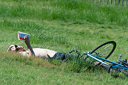 © Licensed to London News Pictures 09/06/2021. Greenwich, UK. A young man sunbathing in the park before going to work. Another hot sunny day in Greenwich park, London as temperatures across the UK are forecast to be hotter than Portugal at the weekend. Photo credit:Grant Falvey/LNP