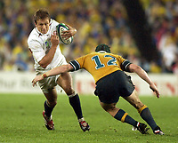 Photo. Steve Holland. England v Australia Final at the Telstra Stadium, Sydney. RWC 2003.<br />22/11/2003.<br />Jonny Wilkinson is tackled by Elton Flatley