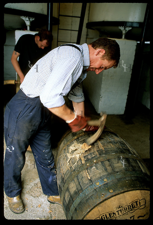 Worker hacks wooden plug flush on newly-filled whisky cask at Glenturret Distillery; Crieff. Scotland