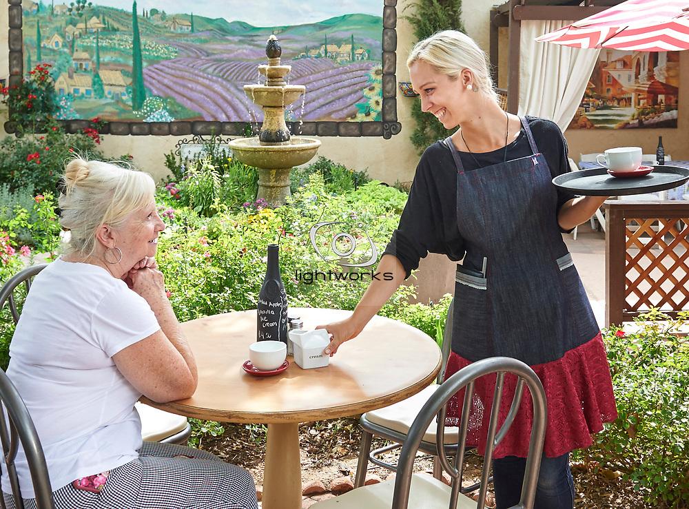 Blonde waitress wearing an apron, serving coffee to an elderly patron at an outdoor sidewalk cafe in Santa Clara, Utah.