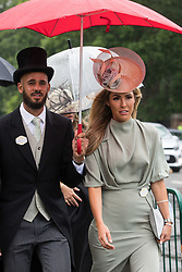 Ascot, UK. 17th June, 2021. Racegoers brave the rain as they arrive on Ladies Day at Royal Ascot. Despite Covid restrictions and changeable weather including some rain, many racegoers displayed the elaborate hats and fascinators for which Gold Cup Day has become well known.