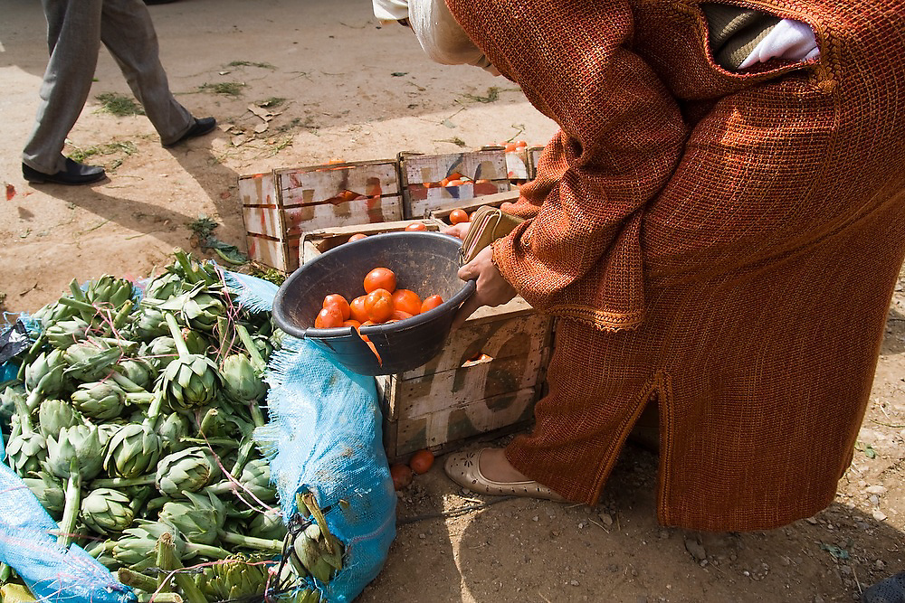 A veiled Muslim woman bends down to pick out tomatoes as a man walks by at the open air market in Chefchaouen, Morocco.