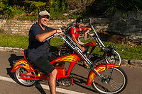 Men riding electric powered chopper bicycles, Manly Beach, Sydney, New South Wales, Australia