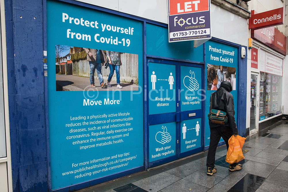 A member of the public passes COVID-19 public information displays on 4 October 2020 in Slough, United Kingdom. Slough Borough Council confirmed on 2nd October that its coronavirus infection rate is the highest in the south of England and Slough MP Tan Dhesi asked Health Secretary Matt Hancock in Parliament whether the local test centre in Montem Lane could be reverted to permit walk-in and drive-in visits without an appointment.