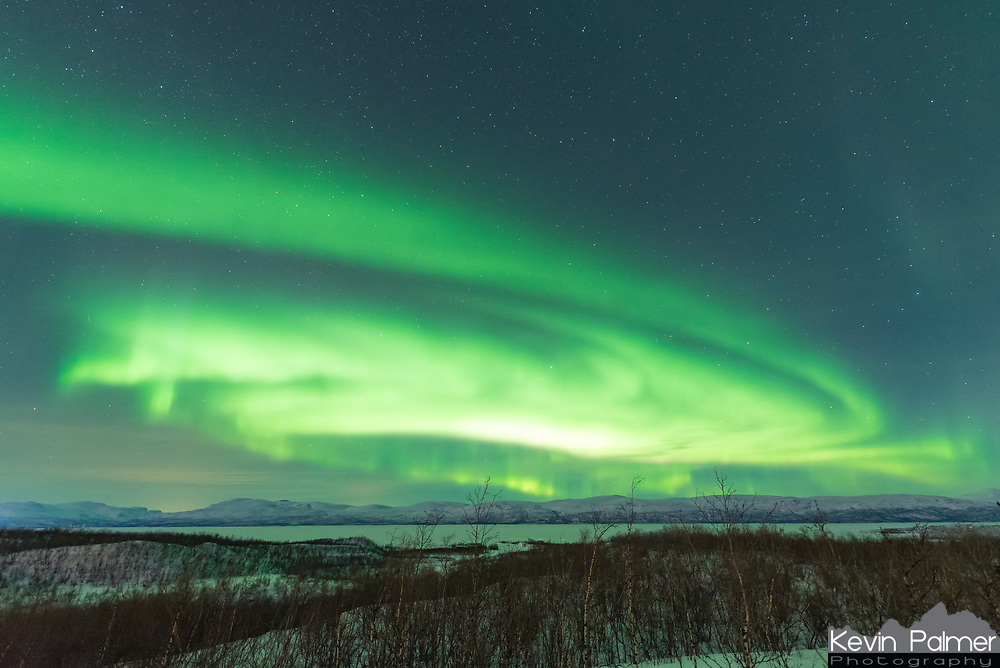 For the 2nd night in a row, there was an active display of the northern lights in Abisko, Sweden. Starting off as a dull glow in the north after sunset, it quickly exploded with bright green spiral swirls filling the entire sky. Here above the Arctic Circle the aurora is ever present, encircling the Earth's poles in a zone called the auroral oval. Even during solar minimum when solar activity is quiet, the northern lights are visible on almost any clear night. And Abisko sees more clear nights than surrounding areas because the mountains to the west create a rain shadow effect. Visible beyond the forest of short birch trees, is Torneträsk, Sweden's 6th largest, and 2nd deepest lake.