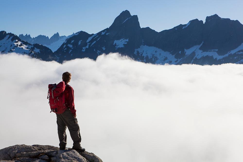 Ian Derrington looks out towards Mount Triumph, the Picket Range, and Mount Despair from Salvation Peak, North Cascades National Park, Washington.