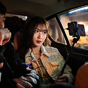 Nai Nai, a 23-year-old live-streamer in Shanghai, China, live-streams while sitting in a taxi with a male fan after her birthday party. Nai Nai's fans are mostly Chinese men between 15 and 30 years old who post messages and virtual gifts, visible to everyone logged on to her chatroom. China's livestreaming industry reached 425 million subscribers in 2018 out of a current total internet user base of more than 829 million, according to government statistics cited in Chinese state media. Livestream hosting is an increasingly popular career choice, especially for young Chinese women like Nai Nai.