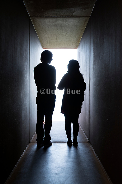 couple standing at the end of the strong light in a tunnel