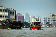 """17 NOVEMBER 2012 - BANGKOK, THAILAND:  Tug boats pull barges up the Chao Phrya River in Bangkok. Bangkok used to be known as the """"Venice of the East"""" because of the number of waterways the criss crossed the city. Now most of the waterways have been filled in but boats and ships still play an important role in daily life in Bangkok. Thousands of people commute to work daily on the Chao Phraya Express Boats and fast boats that ply Khlong Saen Saeb or use boats to get around on the canals on the Thonburi side of the river. Boats are used to haul commodities through the city to deep water ports for export.    PHOTO BY JACK KURTZ"""