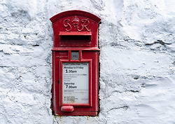 Detail of traditional old red postbox on white wall