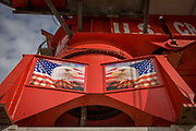 American Eagle flags on crane on construction site in Manhattan, New York City. The red structure is on the roof of a new apartment development in lower Manhattan, New York City. The bald eagle was chosen June 20, 1782 as the emblem of the United States of American, because of its long life, great strength and majestic looks, and also because it was then believed to exist only on this continent.  On the backs of gold coins, the silver dollar, the half dollar and the quarter, we see an eagle's head with the stars and stripes in the background - an image of strength and patriotism.
