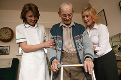 Carers helping to support an elderly man walking with a frame; homecare for the elderly,