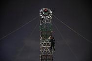 Un pirotécnico sube una torre para revisar su equipo antes de ejecutar un espectáculo pirotécnico.  /  A pyrotechnician climbs a tower to check his equipment before performing a show.