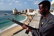 A young man with a gun overlooks the old port area destroyed by fighting in the old Arab quarter in Mogadishu, war-torn capital of Somalia. March 1992.