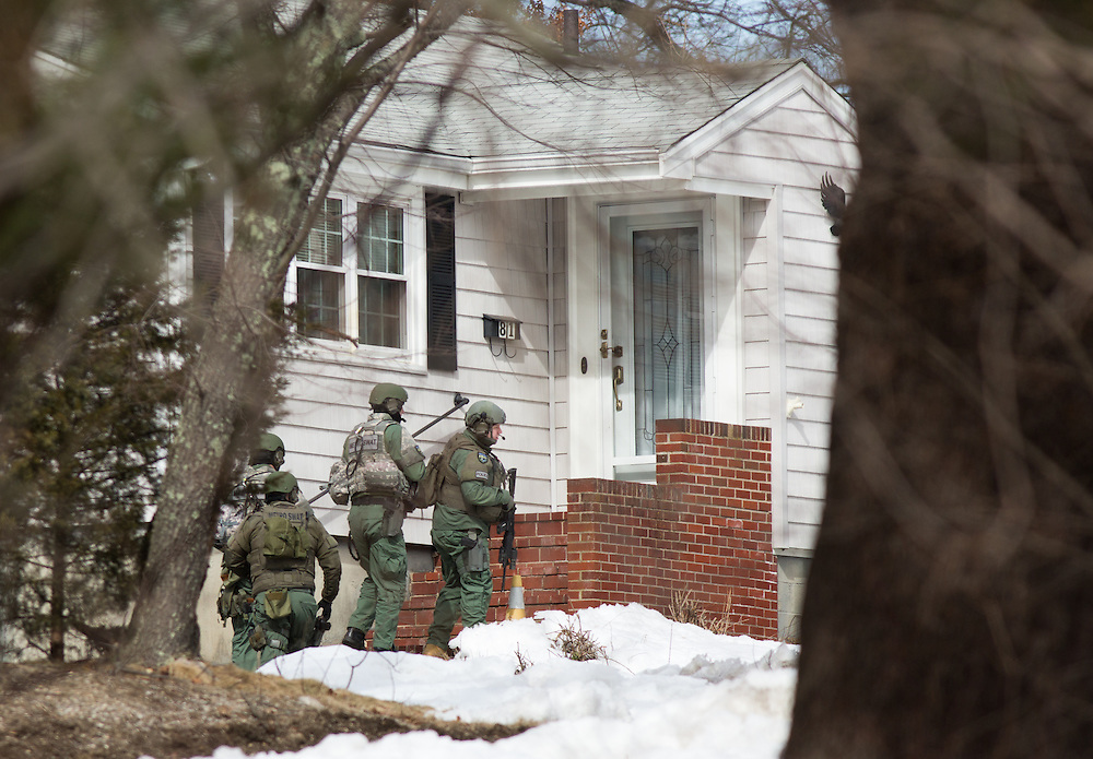 Dedham, MA 03/07/2014<br /> Metro SWAT officers take cover behind a home on Leonard St during a standoff in East Dedham on Friday afternoon.<br /> Alex Jones / www.alexjonesphoto.com