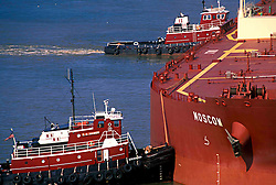 A tanker is nudged into position by two tug boats.
