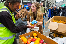 A woman hands out free food as hundreds of environmental protesters from Extinction Rebellion occupy Oxford Circus, a pink yacht being the focal point of their presence, with traffic denied access to two of London's busiest streets. London, April 16 2019.